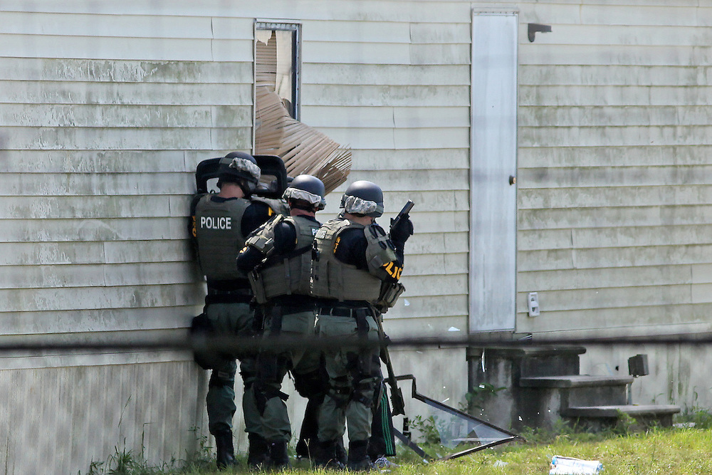 ANDREW KNAPP/STAFF -- Sept. 10, 2012 -- A SWAT team breaks a window to a Remount Road mobile home as the man inside refuses to come out Monday afternoon during a standoff with the North Charleston Police Department.