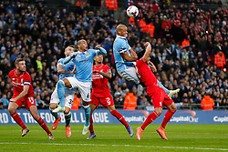 Vincent Kompany of Manchester City heads the ball as Emre Can of Liverpool challenges - Mandatory byline: Rogan Thomson/JMP - 28/02/2016 - FOOTBALL - Wembley Stadium - London, England - Liverpool v Manchester City - Capital One Cup Final.