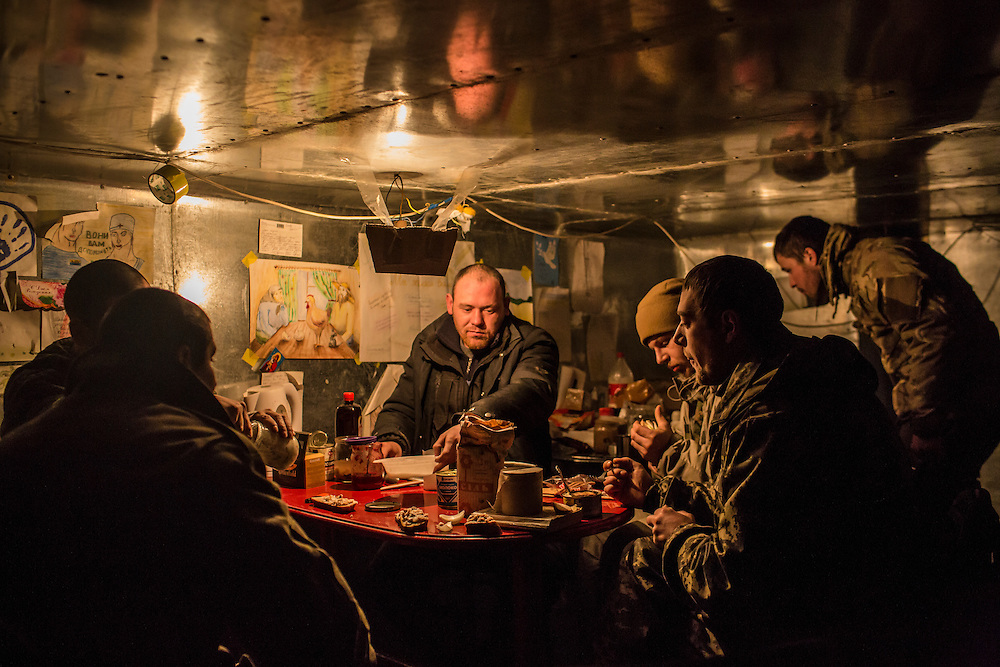 DEBALTSEVE, UKRAINE - FEBRUARY 8, 2015: Ukrainian soldiers eat lunch in an underground bunker in Debaltseve, Ukraine. Fighting between pro-Russia rebels and Ukrainian forces there over the past two weeks has dealt steady casualties to Ukrainian fighters and civilians. CREDIT: Brendan Hoffman for The New York Times