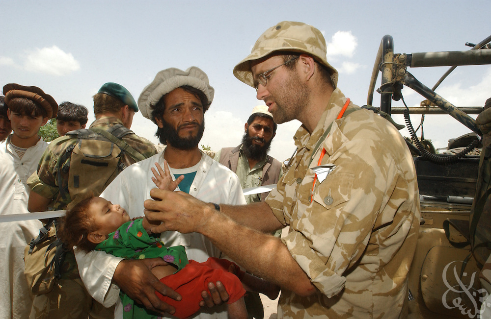 British navy surgeon Lt. James Hayton (R) examines an Afghan infant June 18, 2002 during a civil humanitarian mission in a remote village in southeastern Afghanistan. Britain is expected to begin withdrawal of 1,700 troops currently deployed in Afghanistan by the end of June 2002.