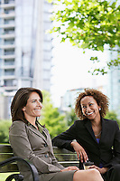 Two business women sitting on park bench smiling