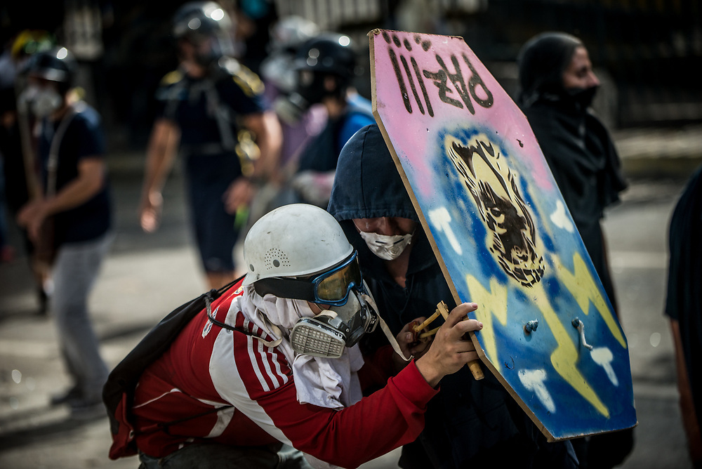 CARACAS, VENEZUELA - MAY 24, 2017:  Anti-government protesters use homemade shields and throw rocks and molotov cocktails at security forces, who responded by heavily tear gassing and firing rubber bullets and buckshot at them.  The streets of Caracas and other cities across Venezuela have been filled with tens of thousands of demonstrators for nearly 100 days of massive protests, held since April 1st. Protesters are enraged at the government for becoming an increasingly repressive, authoritarian regime that has delayed elections, used armed government loyalist to threaten dissidents, called for the Constitution to be re-written to favor them, jailed and tortured protesters and members of the political opposition, and whose corruption and failed economic policy has caused the current economic crisis that has led to widespread food and medicine shortages across the country.  Independent local media report nearly 100 people have been killed during protests and protest-related riots and looting.  The government currently only officially reports 75 deaths.  Over 2,000 people have been injured, and over 3,000 protesters have been detained by authorities.  PHOTO: Meridith Kohut