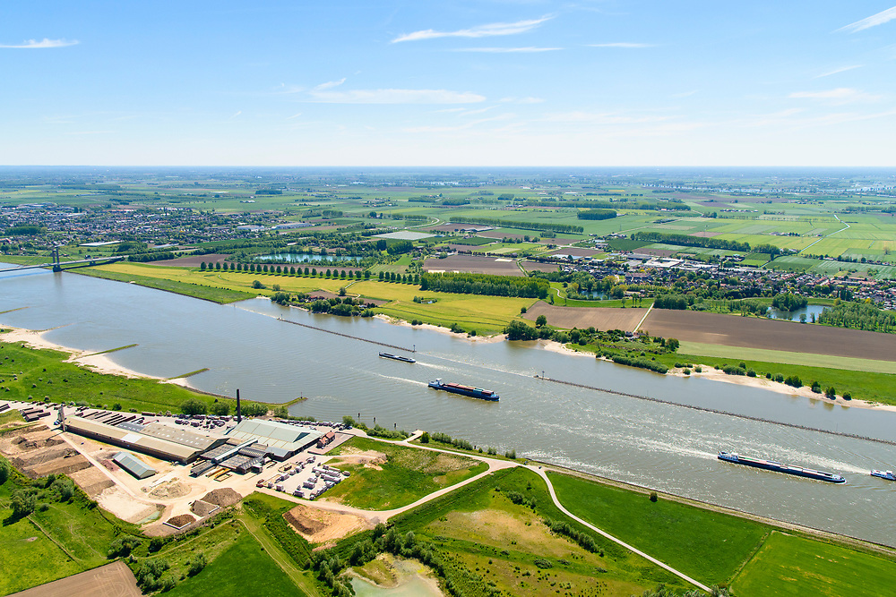 Nederland, Gelderland, Tiel, 13-05-2019; scheepvaartverkeer op rivier De Waal, gezien naar Prins Willem Alexanderbrug, steenfabriek Wienerberger in de voorgrond.<br /> Shipping traffic on river De Waal, seen to Prince Willem Alexander Bridge, brick factory Wienerberger in the foreground.<br /> luchtfoto (toeslag op standard tarieven);<br /> aerial photo (additional fee required);<br /> copyright foto/photo Siebe Swart
