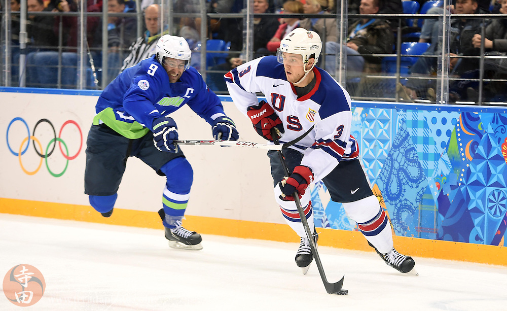 Feb 16, 2014; Sochi, RUSSIA; USA defenseman Cam Fowler (3) skates with the puck past Slovenia forward Tomz Razingar (9) in a men's ice hockey preliminary round game during the Sochi 2014 Olympic Winter Games at Shayba Arena.