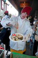 Visitors enjoy raclette outside the House of Switzerland during the 2010 Olympic Winter Games in Whistler, BC Canada.