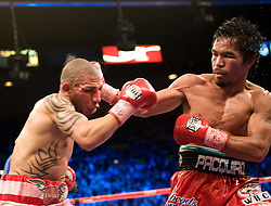 Manny Pacquiao of the Philippines catches Miguel Angel Cotto of Puerto Rico in their WBO Welterweight Championship fight at the MGM Grand Garden Arena on November 14, 2009 in Las Vegas, Nevada. Pacquiao won his seventh world title in as many divisions