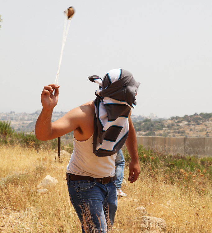 Local Palestinian youth hurls stone from sling shot at Israeli soldiers on Israeli Security Wall dividing Bil'in village, Palestine Territory Occupied