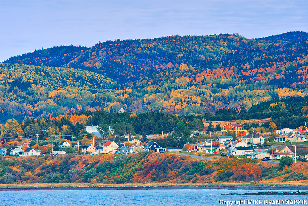 Coastal village and autumn colors of mixedwood forest in the Chic-Choc Mountains (Appalachian Mountains). Boreal Forest Region.<br />