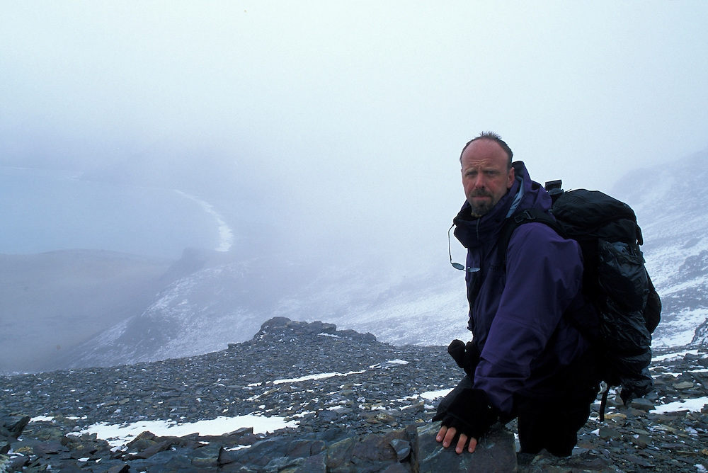 South Georgia Island, (MR) Photographer Paul Souders stands in snowy pass above King Penguin rookery at St. Andrews Bay