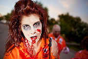 "Oct. 30, 2009 -- PHOENIX, AZ: ASHLEY ATLER leads the Zombies through downtown Phoenix Friday night. About 200 people participated in the first ""Zombie Walk"" in Phoenix, AZ, Friday night. The Zombies walked through downtown Phoenix ""attacking"" willing victims and mixing with folks going to the theatre and downtown sports venues.  Photo by Jack Kurtz"