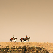 Horses riding along rockface at Giza, Cairo, Egypt (December 2007)
