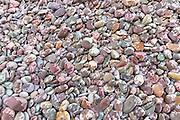Raindrops on pebbles make a splash of colour as rain starts to fall on Bossington Beach, Somerset, UK