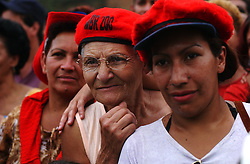 (right to left)Zay Martinez, Pilar Zalmiento and Omaira Marquez listen to President Hugo Chavez as he speaks at the inauguration of a government subsidized market called Mercal.