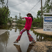 KEY LARGO, FLORIDA, NOVEMBER 15, 2016<br /> Twin Lakes resident Narelle Prew skips a puddle as she walks her chihuahua Lexy on her block which has several areas flooded as a result of the flooding that follows a super moon. This is a regular occurrence in parts of Florida. <br /> (Photo by Angel Valentin/Freelance)