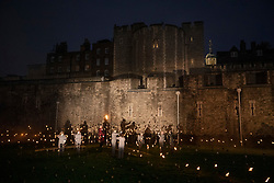 © Licensed to London News Pictures. 04/11/2018. London, UK. Volunteers ignite thousands of individual flames to illuminate the moat of The Tower of London in an installation entitled 'Beyond the Deepening Shadow: The Tower Remembers'. This public act of remembrance for the lives of the fallen, honouring their sacrifice will run for eight nights, leading up to and including the Centenary Armistice Day 2018. The evolving installation will unfold each evening over the course of four hours, with the Tower moat gradually illuminated by individual flames. A specially-commissioned sound installation 'a sonic exploration of the shifting tide of political alliances, friendship, love and loss in war' will be played. At the centre of the sound installation lies a new choral work, with words from war poet Mary Borden's Sonnets to a Soldier. Photo credit: Peter Macdiarmid/LNP