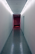 A long hallway with glowing red exit sign at the end.