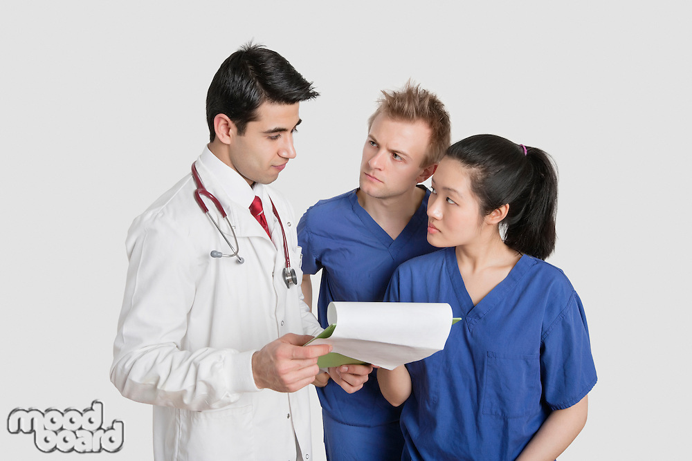 Multi ethnic healthcare professionals discussing medical report over gray background