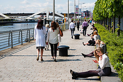 Office workers on lunch break beside the river Clyde at Broomielaw at IFSD new business and financial district in Glasgow United Kingdom