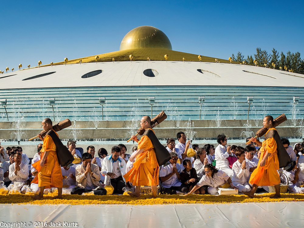 """02 JANUARY 2016 - KHLONG LUANG, PATHUM THANI, THAILAND:  Monks from the Dhammakaya sect walk through the crowd at Wat Phra Dhammakaya on the first day of the 5th annual Dhammachai Dhutanaga (a dhutanga is a """"wandering"""" and translated as pilgrimage). More than 1,300 monks are participating pilgrimage through central Thailand. The purpose of the pilgrimage is to pay homage to the Buddha, preserve Buddhist culture, welcome the new year, and """"develop virtuous Buddhist youth leaders."""" Wat Phra Dhammakaya is the largest Buddhist temple in Thailand and the center of the Dhammakaya movement, a Buddhist sect founded in the 1970s. The monks are using busses on some parts of the pilgrimage this year after complaints about traffic jams caused by the monks walking along main highways.         PHOTO BY JACK KURTZ"""