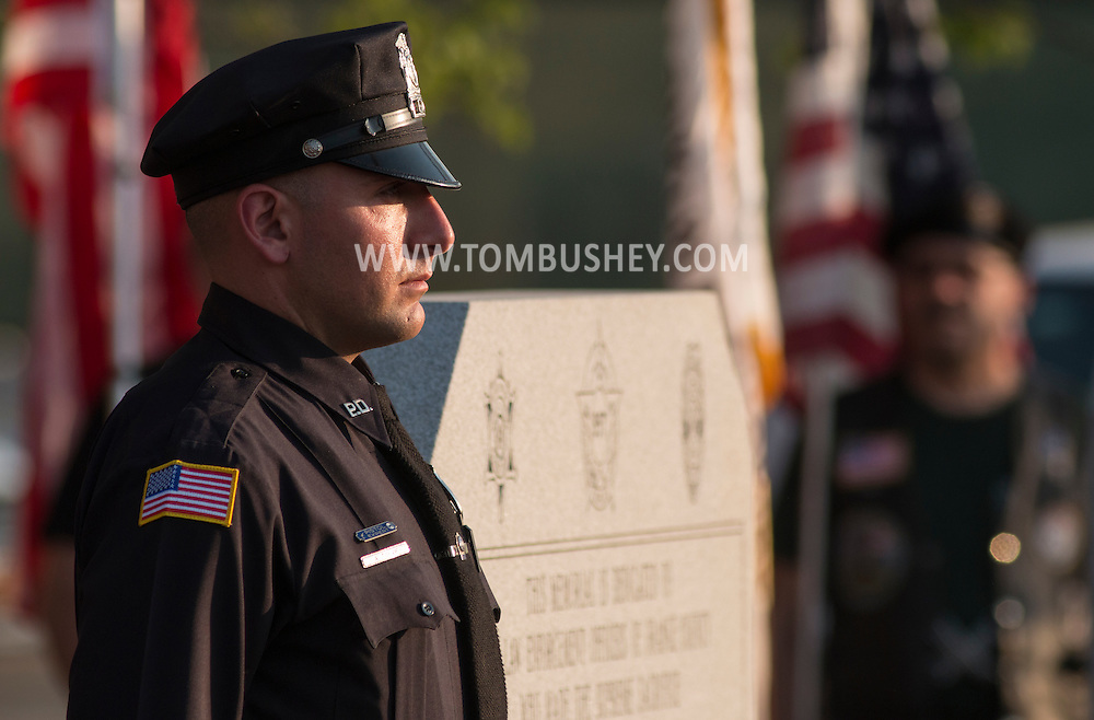 Goshen, New York - A police officer stands at attention by the monument during the Orange County Law Enforcement Officer Memorial Service at the entrance of the Orange County Courthouse on May 8, 2015. The memorial service honors the memory of the members of the Orange County law enforcement community that died in the line of duty. The service also pays tribute the families and loved ones left behind for their courage, dignity and perseverance.
