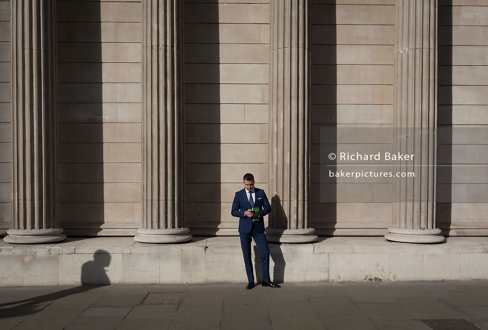 A City businessman checks for messages and uses social media beneath the walls of the Bank of England, on 30th October 2017, Threadneedle Street, in the City of London, England.
