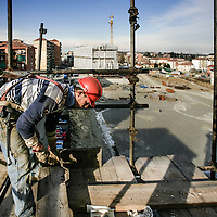 carpentiere al lavoro su una impalcatura di un cantiere edile<br /> <br /> carpenter working on a scaffolding of a construction site
