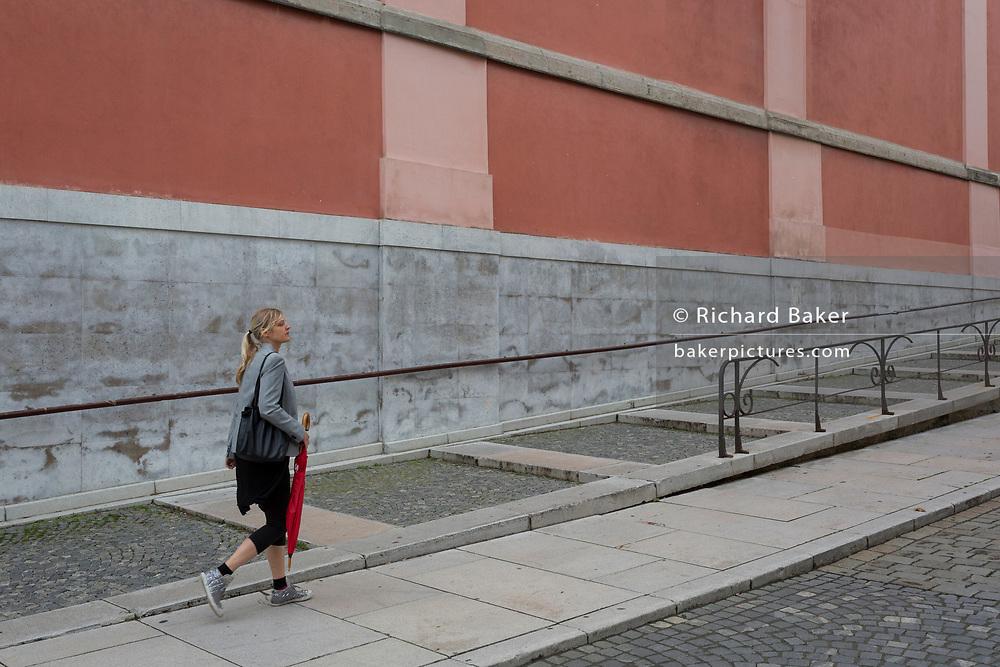 A lady walks up on Miklosiceva Cesta (street) in the Slovenian capital, Ljubljana, on 28th June 2018, in Ljubljana, Slovenia.