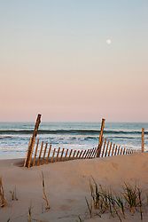 With a full moon at dusk, a weather worn sand dune fence sits in a dune along the Jersey shore,Stone Harbor,New Jersey,USA