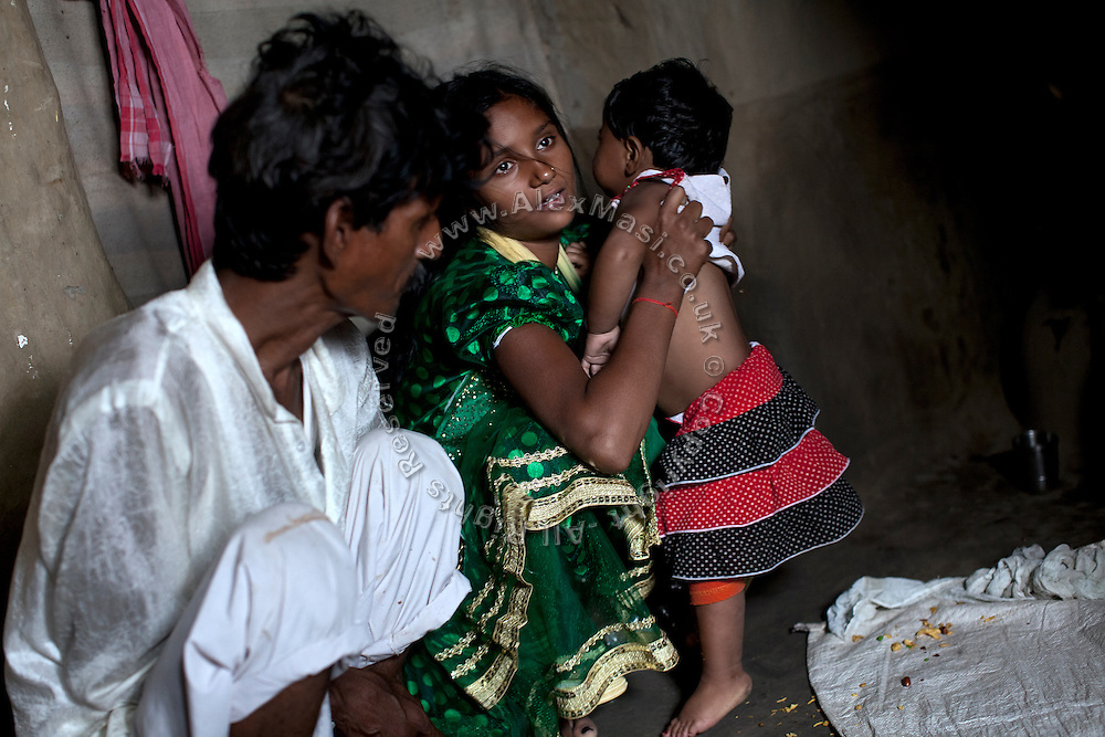 Kanchan Kumari Sharma, 12, (centre) is taking care of her young niece, while sitting next to her father, Raja Kumar Sharma, 45, (left) inside their home in Sersiya Kekrahi village, Varanasi District, Uttar Pradesh, India. In 2012, Kanchan went with a friend to bring lunch to her father, around 2 km away from her home. On the way they met Rajesh (rapist) and Ashok, a friend of his. Both girls were picked up on the spot using an excuse. Ashok drove Kanchan's friend home, but Rajesh forced Kanchan to travel with him during six days and for hundreds of kilometres across different states. (Mirzapur / Chennai / Itarsi / Bhusawal) He raped her once behind the station in Itarsi. With great effort and some coincidence, the uncle of Kanchan managed to bring her back home. Although she was scared, she insisted on going to the police to file a case (FIR). She was kept at the police station for 12 days and threatened to prevent her from filing an official case. Ashok and Rajesh are from higher caste and wealthy families. While Rajesh spent 24 days in jail initially in summer 2012, he is now a free man while the trial is still going on. Kanchan's family is now struggling to put together 30.000 Indian Rupees (500 USD) to continue battling for justice in court.