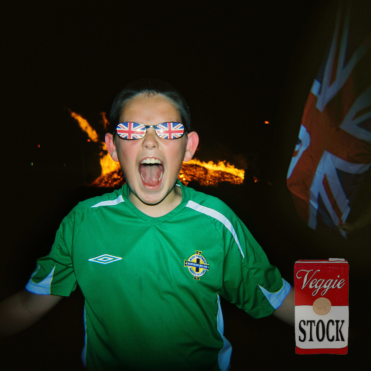 A boy wearing union jack glasses poses for a photo next to a bonfire in Belfast, Northern Ireland, July 2008..The bonfires are built in preparation for the annual 12th July celebrations, which commemorate the defeat of James Stuart at the Battle of the Boyne in 1690.