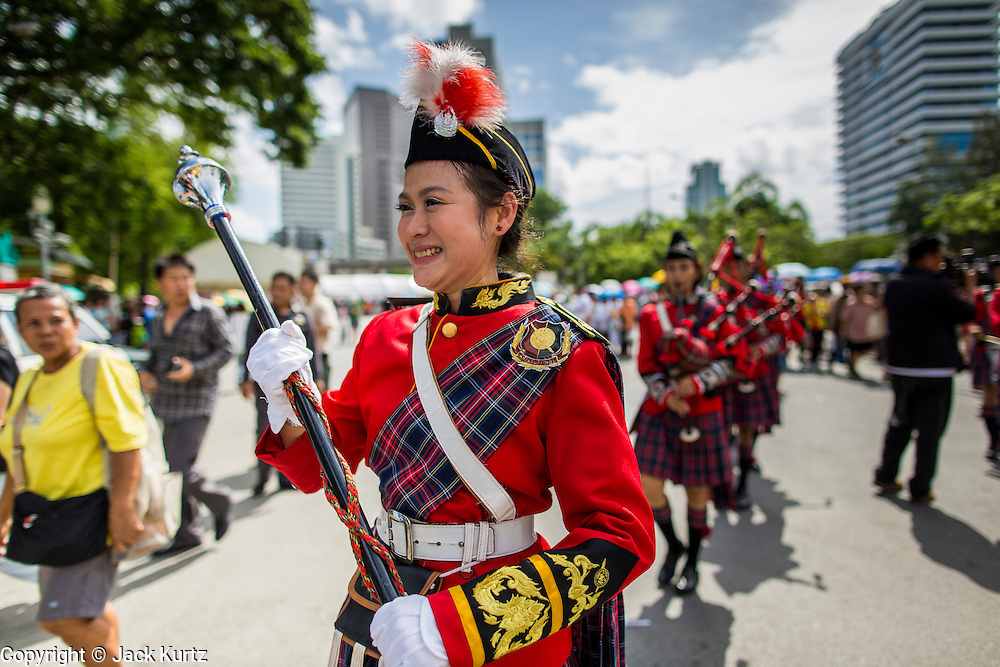 """15 JUNE 2014 - BANGKOK, THAILAND:  A Thai bagpipe band marches through Lumpini Park in Bangkok during a """"Return Happiness to Thais"""" party Sunday. The Thai military junta, formally called the National Council for Peace and Order (NCPO), is sponsoring a series of events throughout Thailand to restore """"Happiness to Thais."""" The events feature live music, dancing girls, military and police choirs, health screenings and free food.  PHOTO BY JACK KURTZ"""