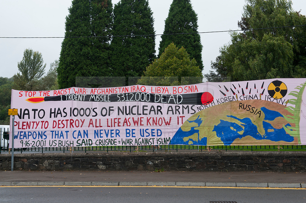 © Licensed to London News Pictures. 29/08/2014. Newport, Gwent, UK. Peace activists unfurl a large protest banner ahead of the summit and anti-war protest marches. 60 World leaders will attend NATO summit at The Celtic Manor on 4th & 5th September. Reportedly approximately 20,000 worldwide Peace Supporters will arrive to take part in a week of peaceful protest and alternative Peace Summit. A 12 mile 'ring of steel' fence is in place at key sites and 9,500 police officers drawn from all 43 police forces in England and Wales. Photo credit: Graham M. Lawrence/LNP
