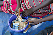 Learning about saving money in communal secure metal boxes for health and education. Visit to the work of Network for Africa in Patongo, Northern Uganda, November 2012.