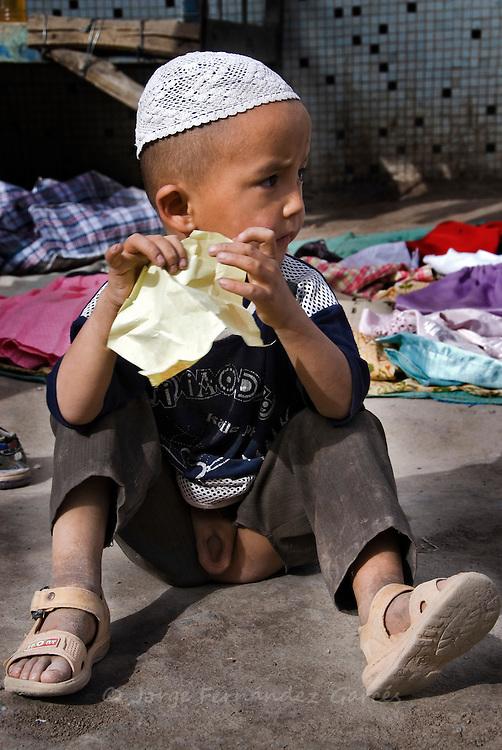 Muslim boy with kid trousers. Kashgar, Xinjiang, China.