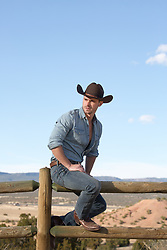 rugged cowboy sitting on a wooden fence on a ranch
