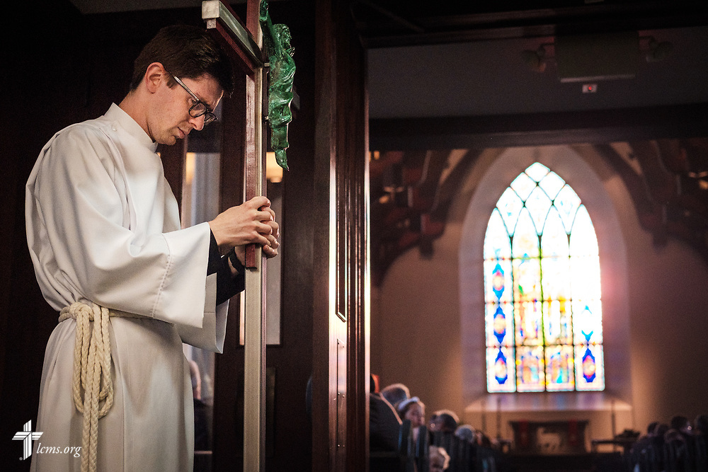The crucifer takes a moment before the start of the Service of Praise with Assignment of Calls in the Chapel of St. Timothy and St. Titus at Concordia Seminary, St. Louis, on Tuesday, April 24, 2018. LCMS Communications/Erik M. Lunsford