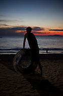 A man with his buoy made of a tire air chamber looks at the  sea in the end of a day, in the beach near Maungmagan village, Dawei, Burma.<br />