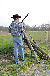 An aging man dressed in western fashions looks the part of a cowboy from days gone by in the American Old West. Accessories include a cowboy hat, boots, denim, sisal rope, western style belt, 12 gauge side by side double barrel shotgun and a saddle blanket on the fence in the background. Wood and Steel fence posts are stacked together with the spares leaning against strands of barbed wire that complete the fence. This image available for EDITORIAL USE ONLY. A release may be required. Additional information by contacting alook at alanlook.com