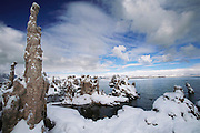 Tufa towers in Mono Lake in winter snow. Mono Lake lie near the town of Lee Vining. It is at least 700,000 years old and one of the oldest continuously existing lakes on the continent. Tufa towers (photographed) are made from calcium and carbonate combine to form limestone, which builds up over time around the lake bottom spring openings. Declining lake levels have exposed the tufa towers we see today. Some of the tufa towers are up to 30 feet high. Route 395: Eastern Sierra Nevada Mountains of California.