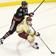 Braden Pimm #14 of the Northeastern Huskies tries to get the puck from Steven Santini #6 of the Boston College Eagles during The Beanpot Championship Game at TD Garden on February 10, 2014 in Boston, Massachusetts. (Photo by Elan Kawesch)