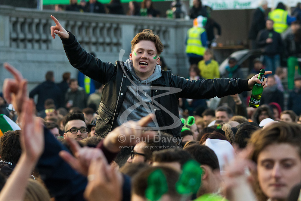 London, March 13th 2016. The annual St Patrick's Day Festival takes place in Trafalgar Square with performances on stage and plenty of Irish food and drink for the thousands of revellers.  PICTURED: Youthful exuberance is helped along by a plentiful supply of beer. ©Paul Davey<br /> FOR LICENCING CONTACT: Paul Davey +44 (0) 7966 016 296 paul@pauldaveycreative.co.uk