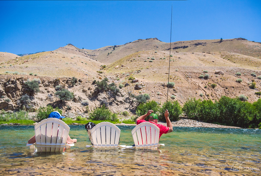 Published in TFFJ Issue 8.2 - Guests of the Flying B ranch on the Middle Fork of the Salmon River take time to drift dries for cuttys in the 'most cool' way possible given the scorching summer sun as their dog keeps watch on the boats passing by in his own lounger.