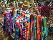 """25 OCTOBER 2015 - INSEIN, MYANMAR: A man sells children's clothes in Danyin Market (also known as Da Nyin) in Insein, Myanmar, about 90 minutes from Yangon. Vendors in the market sell just about everything people in the area need, but mostly it's a """"wet market"""" with fruits, vegetables and meats. Most people in Myanmar still do not have refrigerators in their homes, so people go to market almost every day.    PHOTO BY JACK KURTZ"""