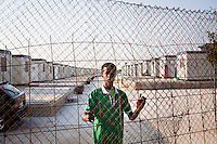 "Hal Far, Malta - 20 August, 2012: Guuleed Abdihe, a 16 years old migrant from Somalia, is in the Hal Far Ten Village open centre at sunrise in Hal Far, Malta, on 20 August, 2012. Gulled arrived in Malta a month ago travelling from Somali by himself.<br /> <br /> The Hal Far Tent Village, initially composed of tents when it first opened, is composed today of 100 containers with no water where the immigrants live for months, and sometimes years. Hal Far (which translates as ""Rat's Town"") is an industrial area of Malta which hosts two open centres for immigrants. The open centres in Malta serve as a temporary accomodation facility, but they ended becoming permanent accomodation centres, except for those immigrants who receive subsidiary protection or refugee status and that are sent to countries such as the United States, Germany, Poland, and others. All immigrants who enter in Malta illegally are detained. Upon arrival to Malta, irregular migrants and asylum seekers are sent to one of three dedicated immigration detention facilities. Once apprehended by the authorities, immigrants remain in detention even after they apply for refugee status. detention lasts as long as it takes for asylum claims to be determined. This usually takes months; asylum seekers often wait five to 10 months for their first interview with the Refugee Commissioner. Asylum seekers may be detained for up to 12 months: at this point, if their claim is still pending, they are released and transferred to an Open Center.<br /> <br /> Gianni Cipriano for The New York Times"