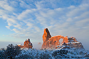 Turret Arch, a prominent natural arch in Arches National Park, Utah, is lit by the rising sun on a foggy winter morning.