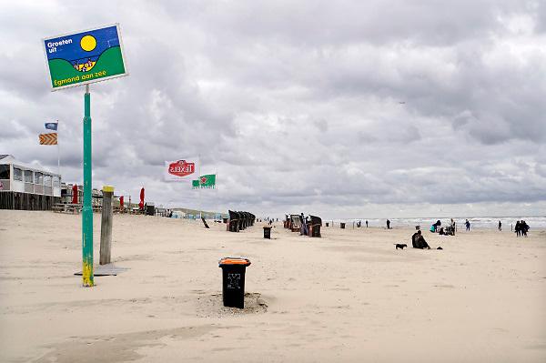 Nederland, Egmond aan zee, 27-8-2018 Strand met en wandelaars . De gemeente Egmond heeft een bord op het strand geplaatst met groeten uit egnond aan zee . Strantent en afvalbak .Foto: Flip Franssen