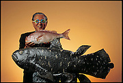 Good-naturedly donning fishy swim goggles for the camera, Yuuzi Terada, an engineer at Mitsubishi Heavy Industries, stands at company headquarters with a pair of the sleek robot fish he constructs. Gray's Paradox asks the question why fish, with their slim muscles and small fins, can accelerate so quickly. Researchers have long hoped that unraveling Gray's Paradox will allow them to build safer, faster nautical propulsion systems. The dream is shared by Terada and other researchers at Mitsubishi, who have long thought that fish fins might serve as a model for a new kind of propeller that would make underwater vehicles faster, more stable, and more maneuverable. Japan. From the book Robo sapiens: Evolution of a New Species, page 106-107.