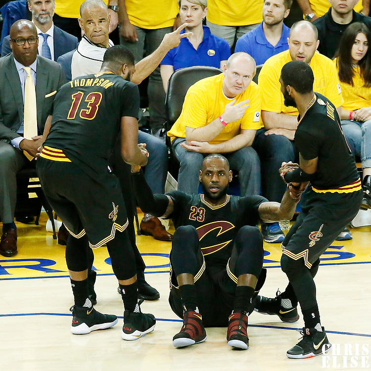 12 June 2017: Cleveland Cavaliers forward LeBron James (23) is helped by Cleveland Cavaliers center Tristan Thompson (13) and Cleveland Cavaliers guard Kyrie Irving (2) during the Golden State Warriors 129-120 victory over the Cleveland Cavaliers, in game 5 of the 2017 NBA Finals, at the Oracle Arena, Oakland, California, USA.