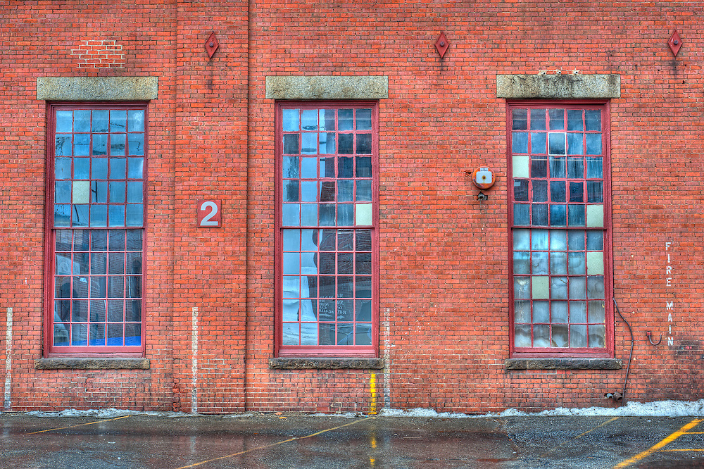 Three windows from a Portland Company building along the waterfront in Portland, Maine