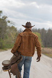 back of a cowboy holding a saddle as he walks down a dirt road
